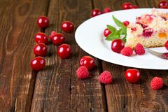Several raspberries and cherries around white plate with cake. Horizontal photo of few cherries and raspberries on wooden board table in front of white plate Royalty Free Stock Photos