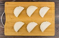 Several raw cottage cheese patties on cutting board on table Royalty Free Stock Image