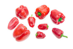 Several red bell peppers different sizes on a light background Stock Photo