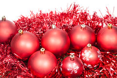 Several red Christmas baubles and tinsel isolated Royalty Free Stock Photo