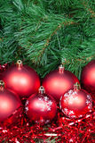 Several red Christmas baubles tinsel and Xmas tree. Vertical Christmas still life - several red Christmas baubles, tinsel on Xmas tree background Royalty Free Stock Photography