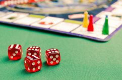 Several red dice for board games on a green background royalty free stock images