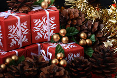 Several red gift boxes among pine tree fir cones Stock Images