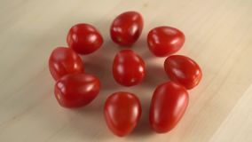 Several red juicy cherry tomatoes are spinning on a wooden surface. A stream of water for washing drops from above. Cooking vegan dishes stock footage