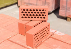 Several red perforated bricks against of pallets of bricks closeup Royalty Free Stock Photo