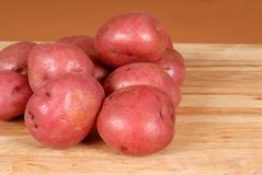 Several red potatoes piled on a cutting board Stock Image