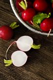 Several red radishes on a wooden board. Several red radishes in a sieve a some radishes on a wooden board Stock Images