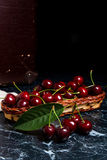 Several red sweet cherries and big green leaf on the table. Fresh organic cherry in yellow wooden basket on dark marble. Close up view of several red sweet royalty free stock image