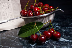 Several red sweet cherries and big green leaf on the table. Fres Stock Photography