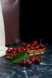 Several red sweet cherries and big green leaf on the table. Fresh organic cherry in yellow wooden basket on dark marble. Close up view of several red sweet royalty free stock images