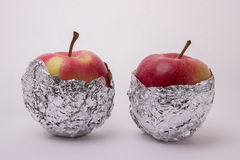 Several red and yellow ripe apples, wrapped in foil on a white b. Several red and yellow ripe and juicy apples, wrapped in foil on a white background Royalty Free Stock Image