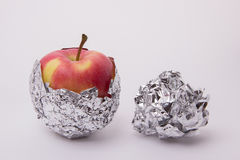 Several red and yellow ripe apples, wrapped in foil on a white b. Several red and yellow ripe and juicy apples, wrapped in foil on a white background Royalty Free Stock Photos