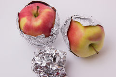 Several red and yellow ripe apples, wrapped in foil on a white b. Several red and yellow ripe and juicy apples, wrapped in foil on a white background Stock Image