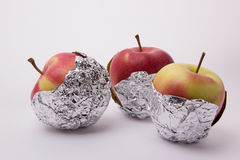 Several red and yellow ripe apples, wrapped in foil on a white b. Several red and yellow ripe and juicy apples, wrapped in foil on a white background Stock Images
