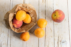 Several ripe apricots and peachs in the kraft bag. Healthy eatin Royalty Free Stock Photo