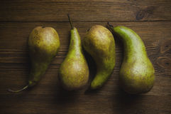 Several ripe pears lying on a wooden textural background Stock Image