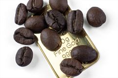 Several roasted coffee beans on an ingot of 999.9 gold. On white Royalty Free Stock Photos