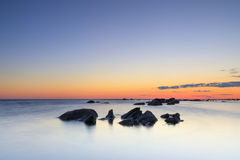 Several rocks in quiet sea at sunset. Several rocks in calm sea at summer sunset Stock Image