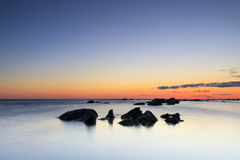 Several rocks in quiet sea at sunset. Several rocks in calm sea at summer sunset Stock Photos