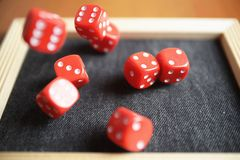 Several rolling red dice fall on special boardgame frame.  Royalty Free Stock Photo