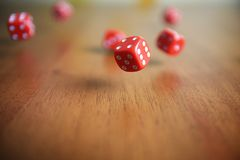 Several rolling red dice fall on a table.  Royalty Free Stock Images