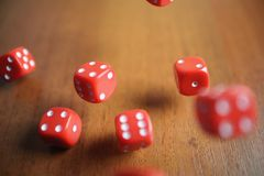 Several rolling red dice fall on a table.  Stock Photos
