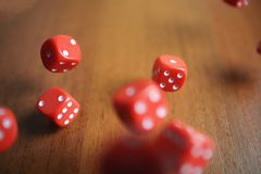 Several rolling red dice fall on a table.  Royalty Free Stock Photography