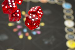 Several rolling red dice fall on a table with boardgame. Gameplay moments.  stock photography