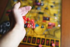 Several rolling red dice fall on a table with boardgame. Gameplay moments Royalty Free Stock Photo