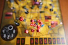 Several rolling red dice fall on a table with boardgame. Gameplay moments Royalty Free Stock Images