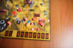 Several rolling red dice fall on a table with boardgame. Gameplay moments.  Stock Image