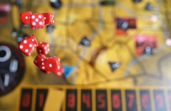 Several rolling red dice fall on a table with boardgame. Gameplay moments Royalty Free Stock Photos