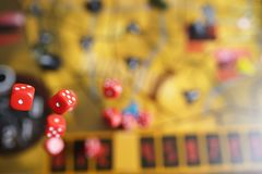 Several rolling red dice fall on a table with boardgame. Gameplay moments.  Royalty Free Stock Photography