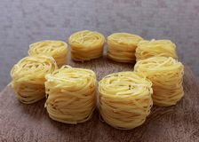 Several round nests of pasta. On gray background stock images