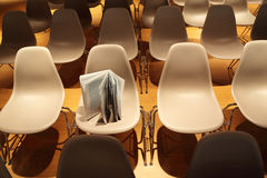 Several rows of chairs; brochure standing on chair Stock Photos