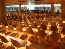 Several rows of white plastic chairs stock photos