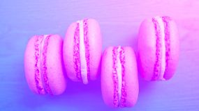 Several Rozovyj cake on a blue wooden background. Macaroons, the concept of taste and pleasure.  Stock Photography