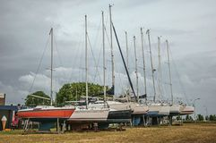 Several sailboats collected in brackets for repair in an open area on cloudy day at Drimmelen. A lovely small hamlet with harbor and elegance streets. Southern Royalty Free Stock Photo