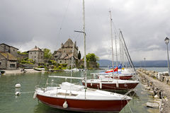 Several sailboats at the port in Yvoire. YVOIRE, FRANCE - MAY 24, 2013: Several sailboats moored along the stone pier at the port on Lake Geneva. On the shore of Royalty Free Stock Photo