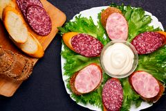 Several sandwiches with sausage and salami and sauce on a plate, flat lay stock images