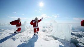 Several Santa Claus Passes Glacial Horses. Christmas holidays, Santa Claus walks around the lake Baikal, Siberia, Russia stock video footage