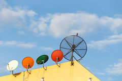 Several satellite dish installed on the house roof with blue sky Royalty Free Stock Image