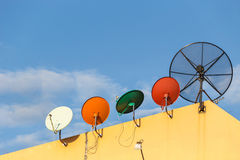 Several satellite dish installed on the house roof with blue sky Stock Photos