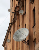 Several satellite dishes on rise old house Royalty Free Stock Photos