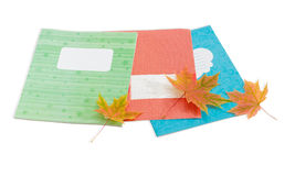Several school exercise book and yellowed maple leaves Royalty Free Stock Photo