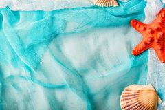 Seashells and starfish on cian cloth background royalty free stock images
