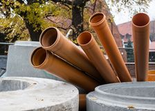Several sewer pipes are lying on the street. Urban landscape stock images