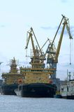 Several ships and harbour cranes. Several ships load cargo on board by harbour cranes Stock Photography