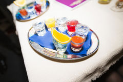 Several shot glasses on silver tray. In bar setting stock photography