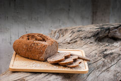 Several slices of Bread wheat and wooden chopping board Royalty Free Stock Photo